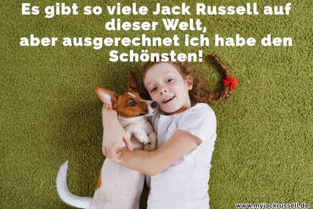 Ein Mädchen liegt mit ihrem Jack Russell auf dem Gras