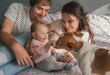 Happy family with cute baby playing whis jack russel dog in bed at home.