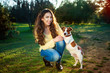 outdoor portrait of beautiful girl and the pet dog Jack Russell terrier.