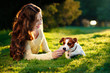 young attractive brunette woman playing with her dog in green park at summer, lifestyle people concept